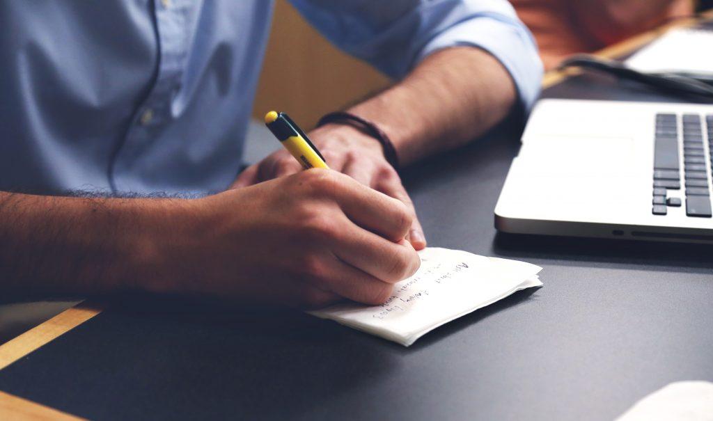 Man taking notes on paper using yellow pen